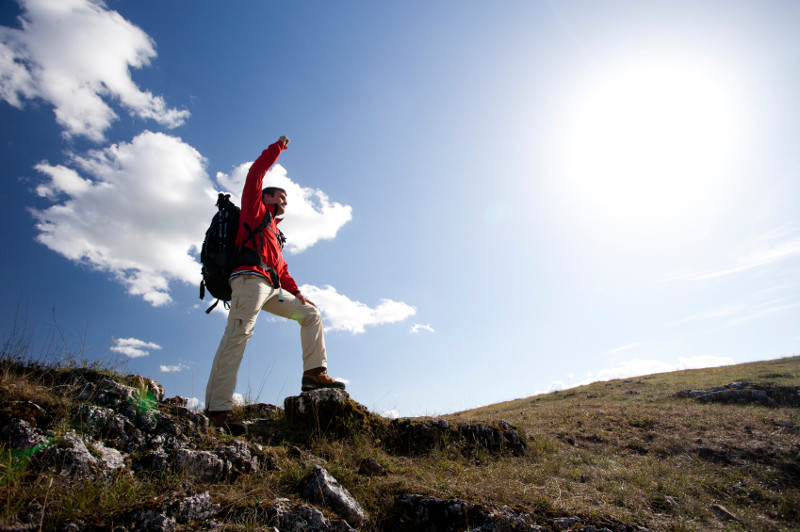 a man, apparently on a hike, with his arm stretched up in a triumphant gesture. Behind him the sky is bright.