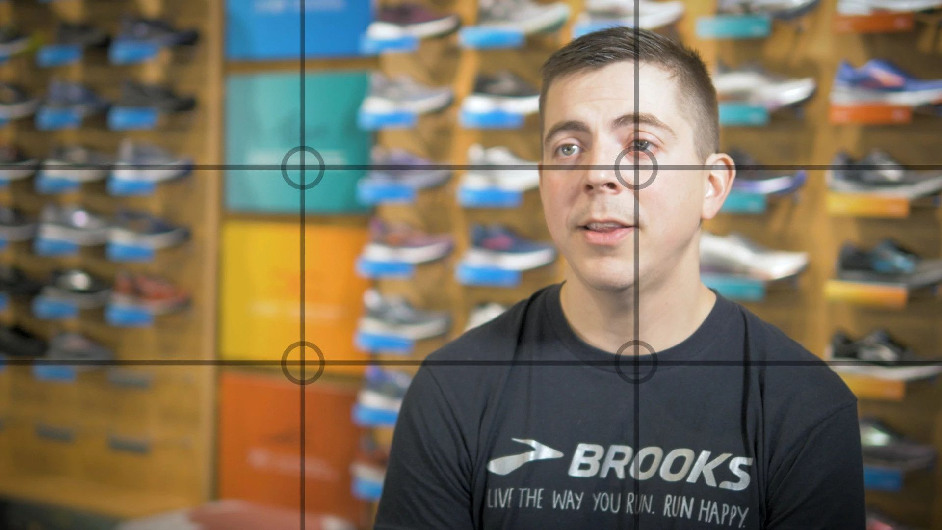 Still video frame of a customer case study interview with lines on the screen depicting the rule of thirds. The still is of a man in a black Brooks Running t-shirt with a wall of shoes blurred out in the background.