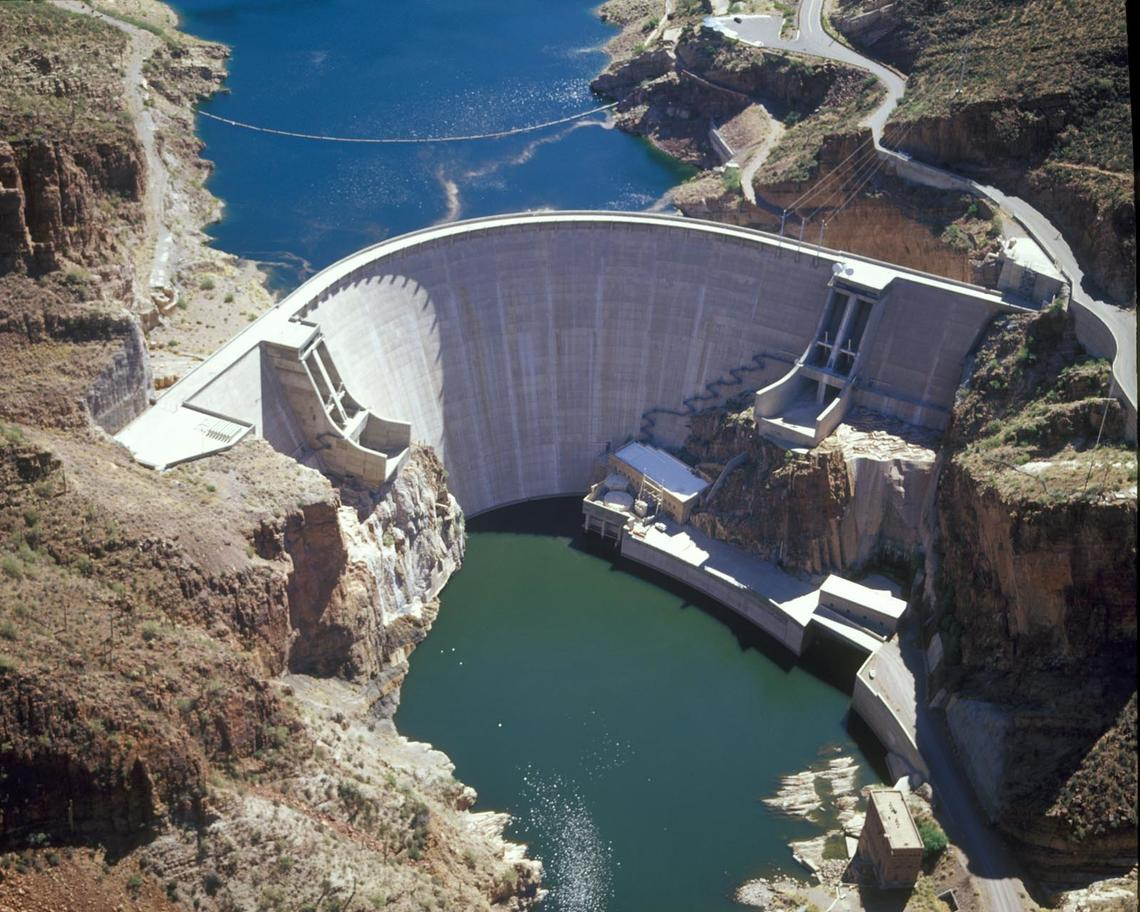Arial image of the Roosevelt dam with desert landscape on both sides and dam in the middle with water on the top and bottom.
