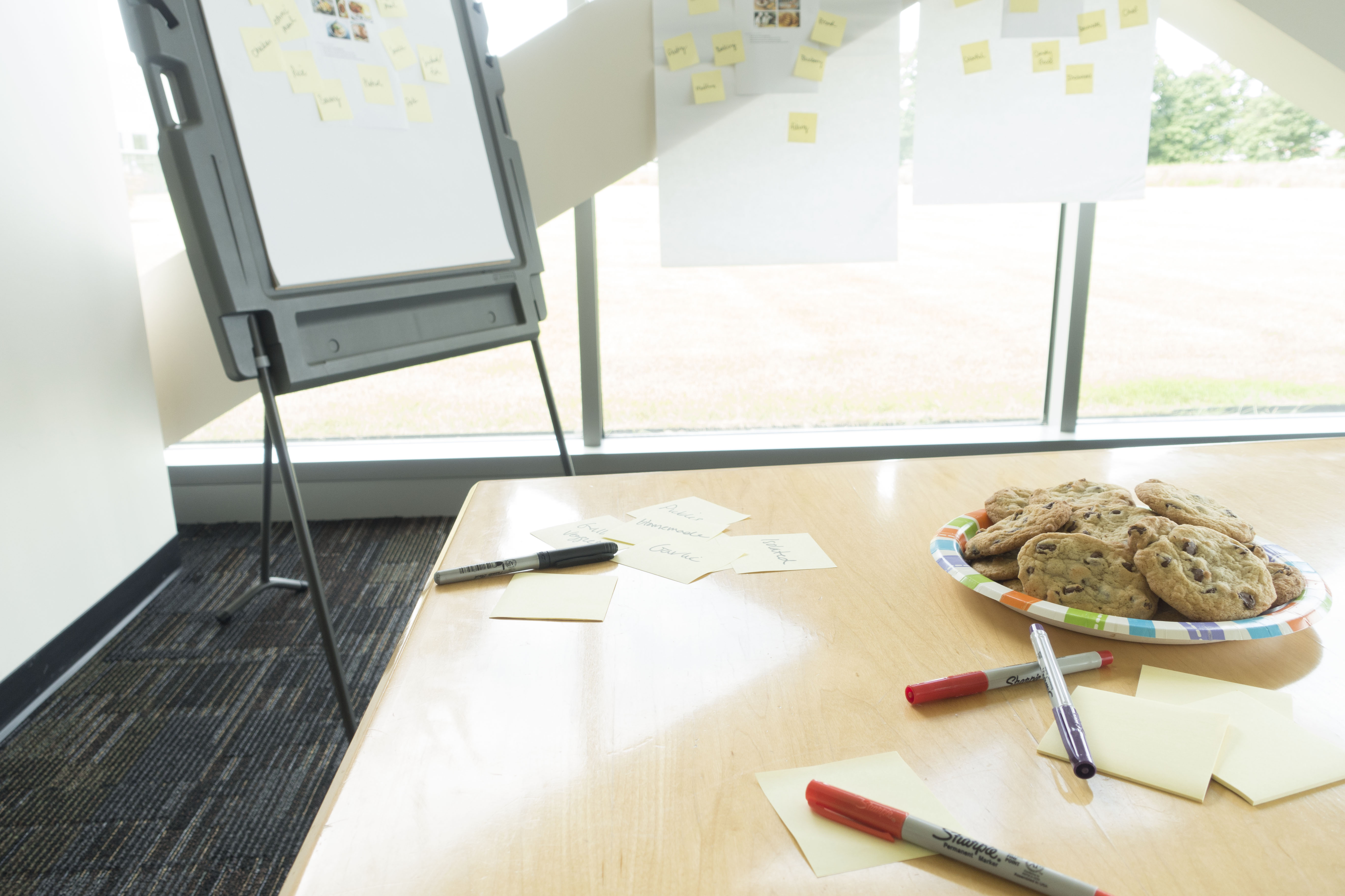 metadata brainstorm exercise with post-it notes and cookies