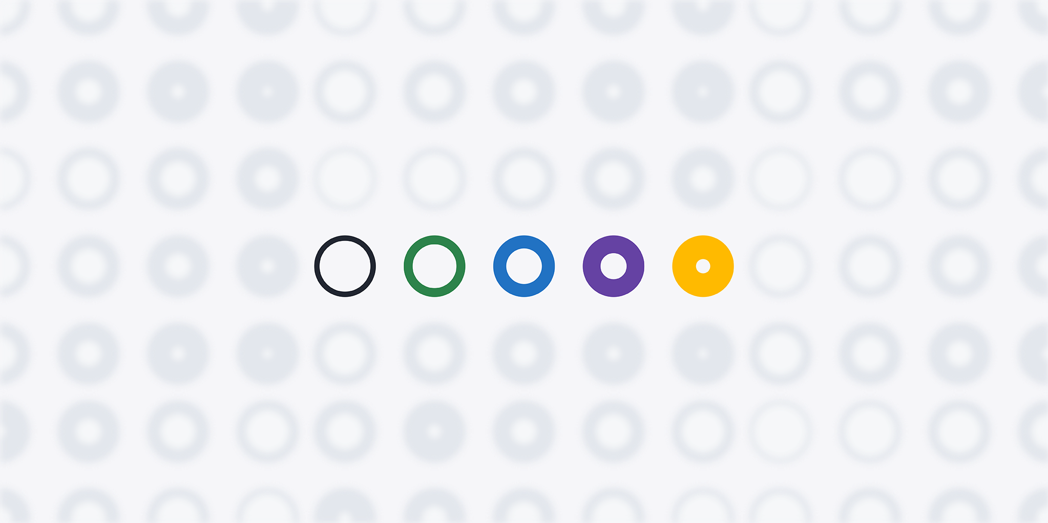 Five colorful, in-focus circles on a background of out of focus gray circles. All with varying space in the middle of the circle.