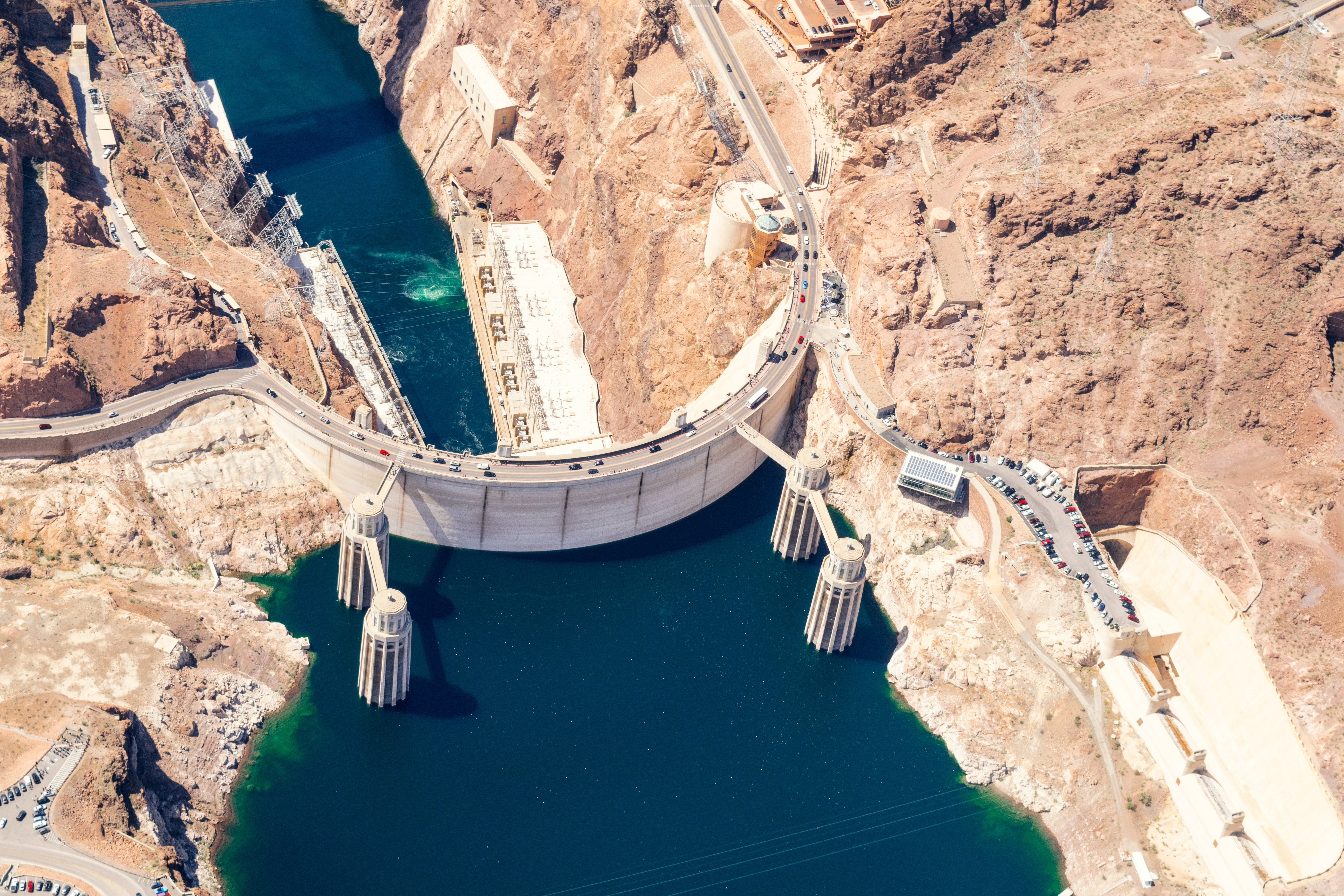 Arial view of the Hoover Dam with brown rock and desert on each side and blue-green water on both sides of the dam.