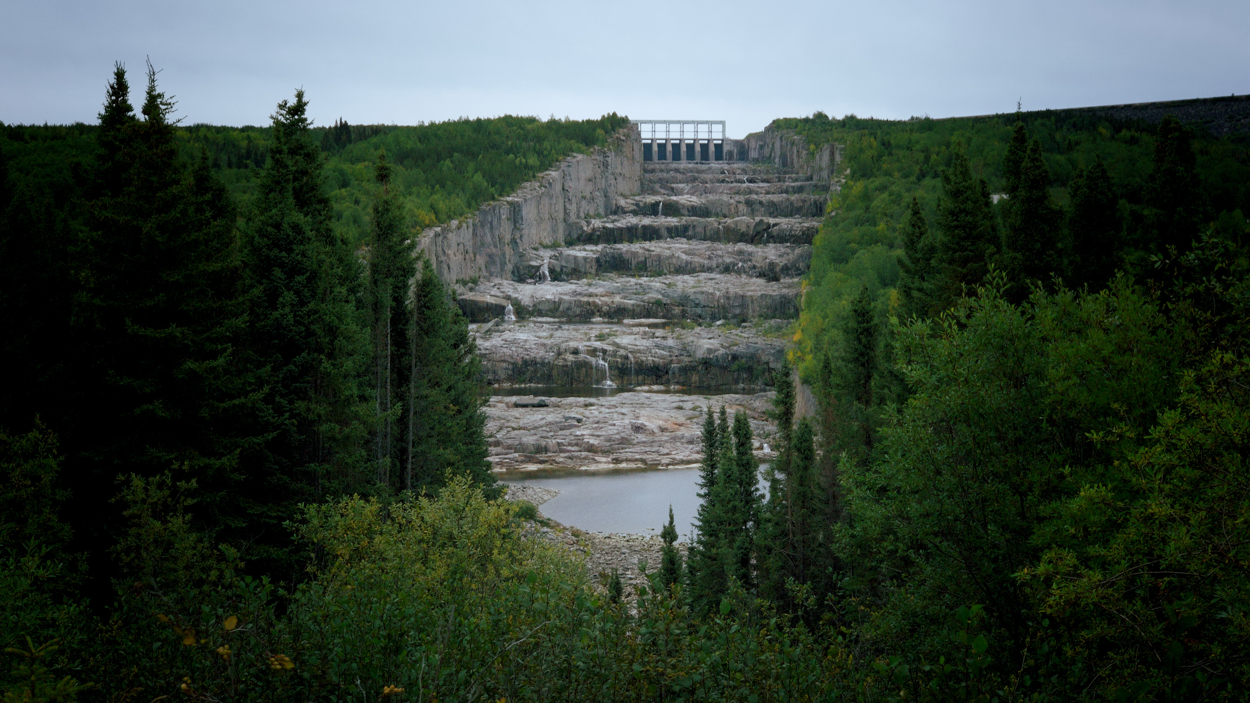 A picture of the Robert-Bourassa Dam with green grass and trees on each side and dam at the top, center of the image with stepped rocks in the middle.