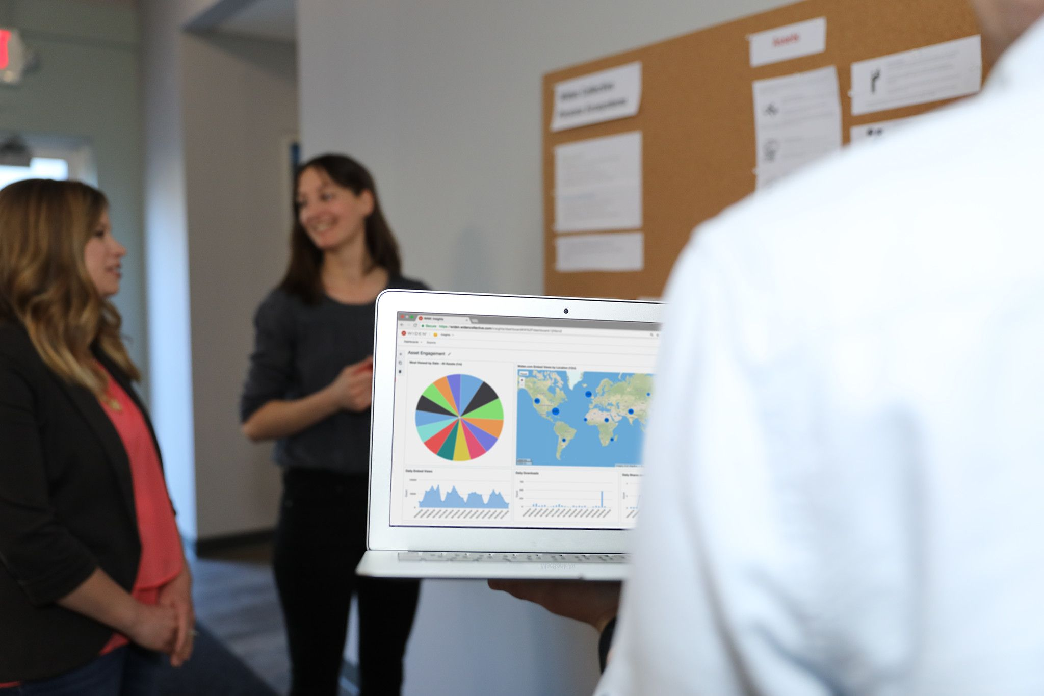 Two women out of focus, talking in the background. With a person whose back is to the camera holding a laptop open to the Widen Collective Insights app in the foreground of the photo.